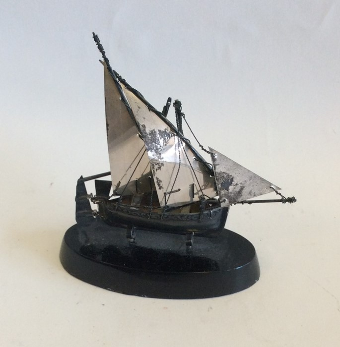 Lot 21 - A small silver model of a junk on ebony stand. App