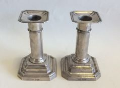 A pair of Edwardian silver candlesticks with cut c
