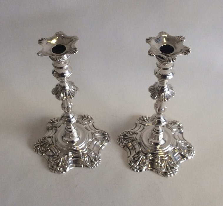 Lot 28 - A good pair of cast silver taper candlesticks with
