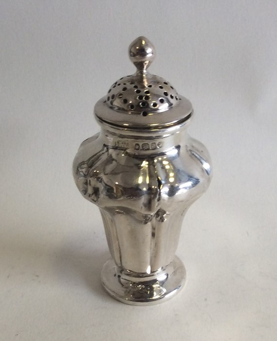 A shaped silver pepper with lift-off cover. London