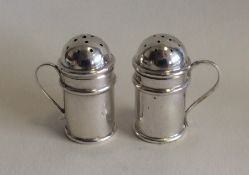 A matched pair of silver pepperettes of churn form