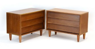 A pair of 1970's teak three-drawer chests, on later circular legs, w.