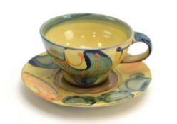 A studio pottery cup and saucer with yellow and blue glazes, moulded RW to base,