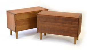 A pair of 1970's teak three-drawer chests, one with a fitted cutlery drawer, on later circular legs,