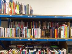 Shelf containing a selection of hard back and paperback novels, reference and other books.