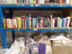 Shelf containing various hardback and paperback novels, self help books etc