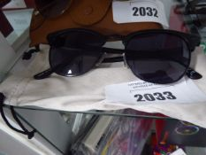 Pair of sunglasses with black frames and soft carry case