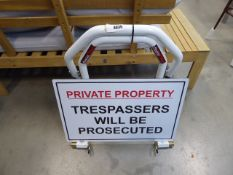 White motorbike stand and a 'Private Property : Trespassers will be prosecuted' sign