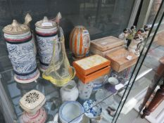 Shelf of assorted household decorative items to include blue and white tankards, painted egg
