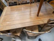 Oak dining table with 6 rush seated chairs