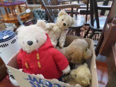 Box containing push along toy dog, paddington bear and other teddy bears