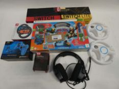 Bag containing Switch & Switch Lite Orzly carry cases, Xbox 360 Skylander set, headset, Wii steering