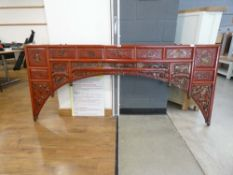 A late 20th century Oriental panel, painted red and decorated with traditional figures and