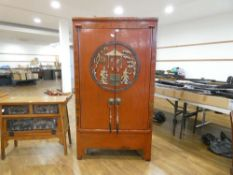 A late 20th century Oriental two door hall cabinet, painted red and decorated with traditional