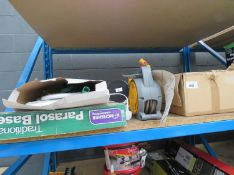 Half shelf containing outdoor lights, small hose reel, parasol base and a light