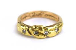 A yellow metal knot-type band ring set four small diamonds, ring size P 1/2, 5.