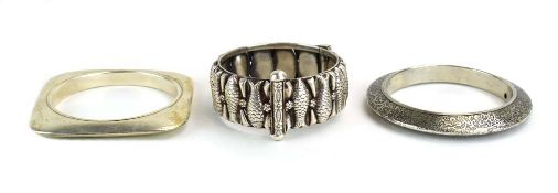 A late 20th century Continental metalware hinged bracelet relief decorated with stylised fish and