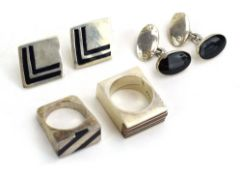 A late 20th century silver ring of square form decorated with bands of black enamel and carnelian,