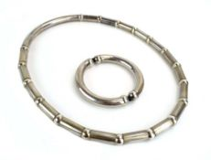 A late 20th century silver necklace having tubular sections on an expanding strap, maker Va,