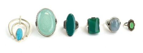 Five silver and metalware dress rings, each set green coloured stones,