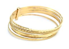 A 9ct yellow gold seven band bangle, each with different engraved decoration, maker LJI,