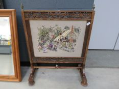 Heavily carved Victorian fire screen, with embroidered insert