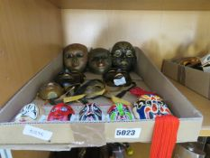 A box containing a quantity of Japanese and Venetian-style ornamental masks