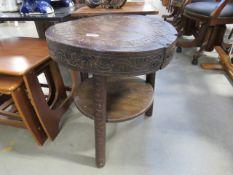 A circular dark oak 2 tier table