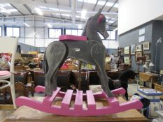 A grey and pink painted child's rocking horse