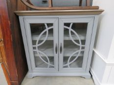 A grey painted glazed double door storage cabinet