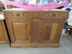 An oak sideboard with carved panels