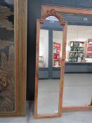 A narrow mirror in pine frame
