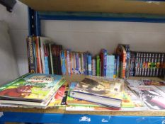 Shelf comprising of selection of children's books, puzzle books, graphic novels, comic books etc