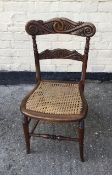 Antique carved back Victorian chair with caned seat.