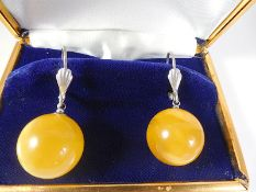 Silver earrings with natural amber ball