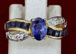 Yellow Metal Oval Tanzanite & Diamond Crossover Style Ring