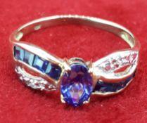 Yellow Metal Oval Tanzanite & Diamond Crossover Style Ring