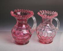 2 Roseglas-Karaffen (um 1890/1900), je m. Reliefdekor, H. je ca. 25 cm. KeineBeschädigungen