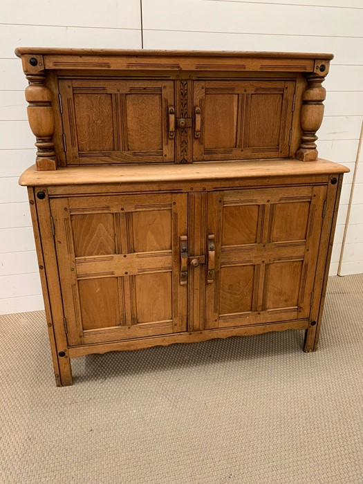 Lot 300 - A light oak sideboard with cupboard top and bottom and turned decorative pillars to side. (H124cm