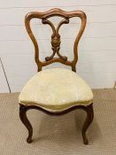 Walnut hall chair on scrolled feet and upholstered seat.