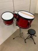 A red children's drum kit with stool