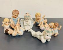 Eight china cherubs of various sizes