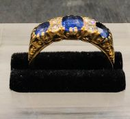 An 18 ct yellow gold three stone Sapphire and Diamond Ring