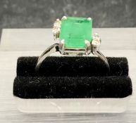 An Emerald ring with diamond shoulders on white gold band marked 750