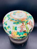 A Chinese porcelain jar and cover decorated with birds and flowers sitting on a stand.