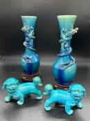 An Oriental pair of Dragon themed vases on stands along with a pair of Foo Dogs.