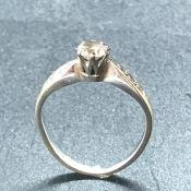 An 18ct white gold ring with central diamond and three stone diamond shoulders.