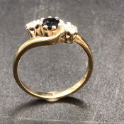 A 9ct gold ring with central sapphire and diamond shoulders.