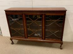 A mahogany display case with three glazed doors on ball and claw feet (H108cm W150cm D34cm)