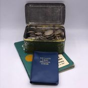 A selection of British pre-decimal coins, including some silver in a parrot boot polish tin and